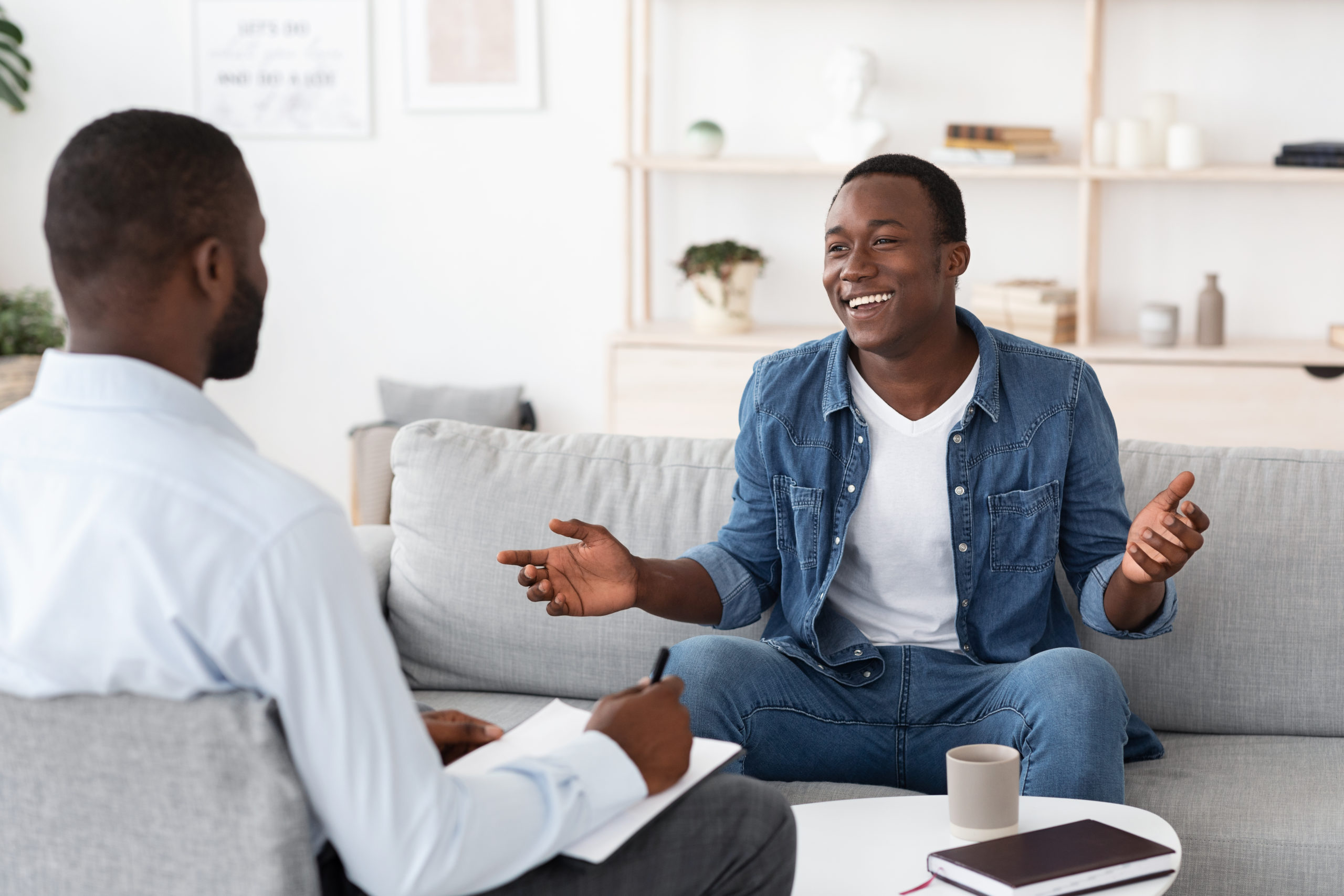 Cheerful black man talking to psychologist and sharing his progress.
