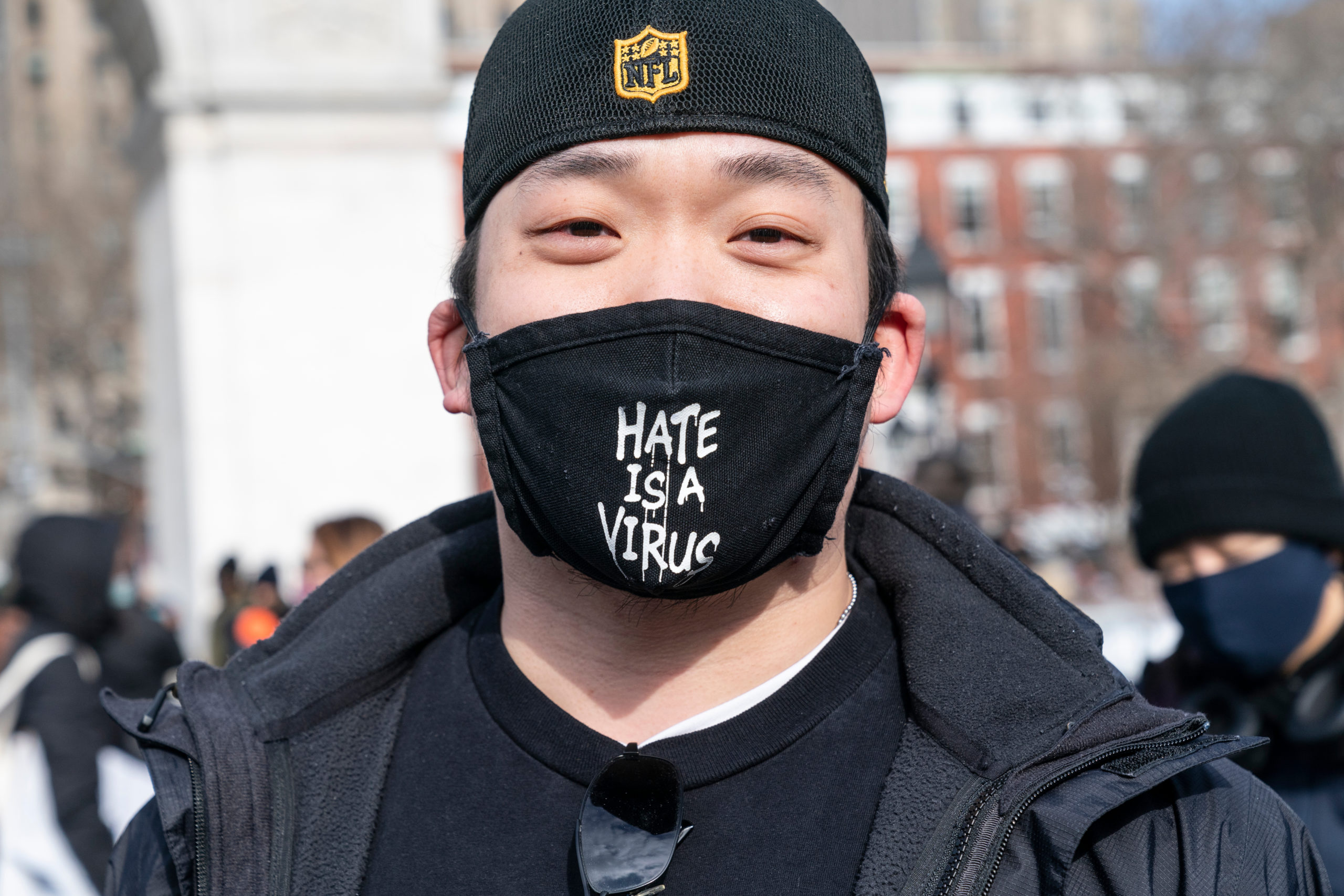 "Man wearing face mask emblazoned with ""Hate is a Virus"""