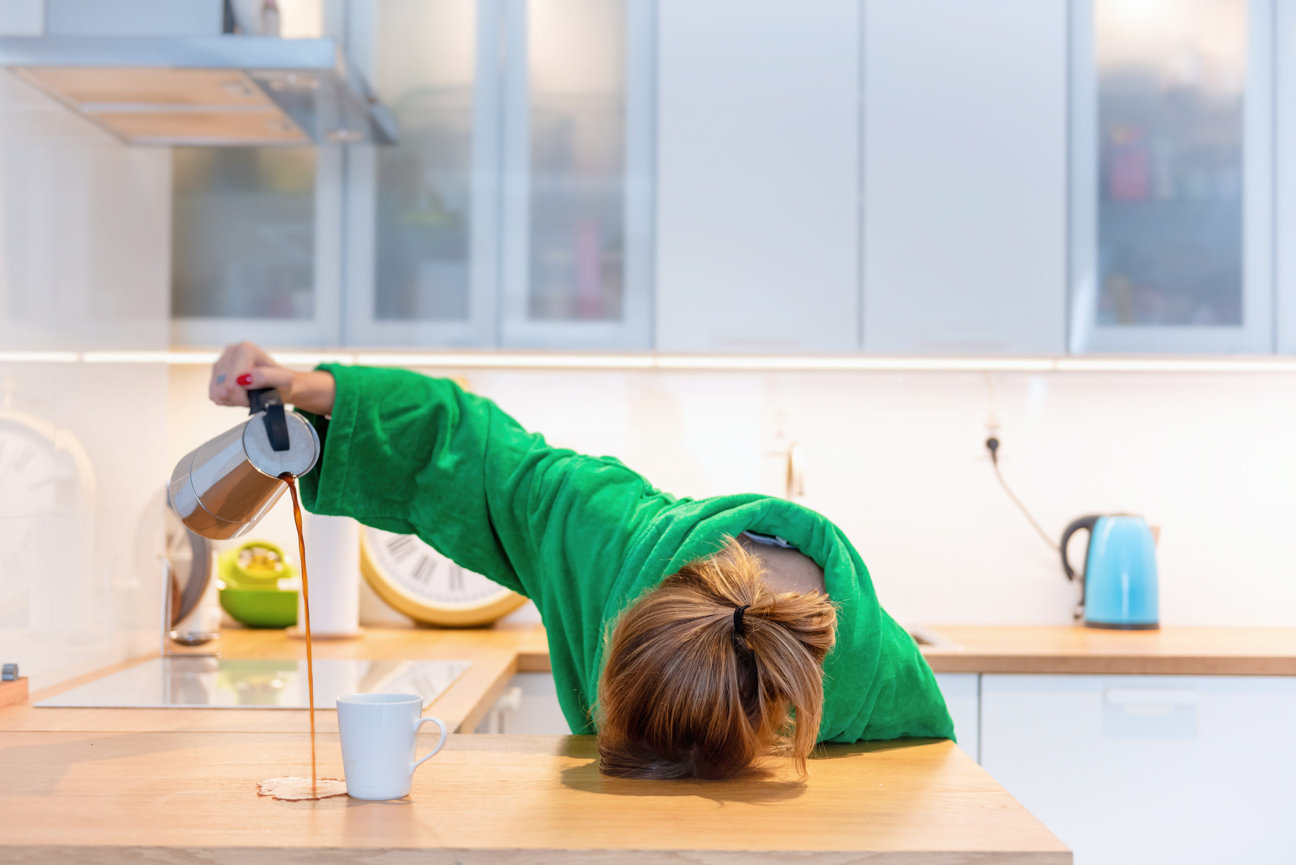 Exhausted woman spilling coffee.